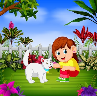 Linda garota brinca com seu gato perto da cerca