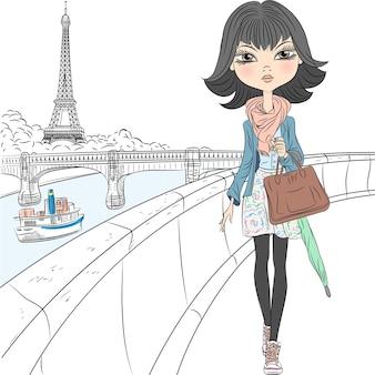 Linda garota da moda em um lenço com um guarda-chuva e uma bolsa caminhando à beira-mar com vista para a torre eiffel em paris