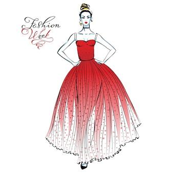 Linda garota na moda em um vestido longo vermelho com bolinhas padrão e inscrição na semana da moda