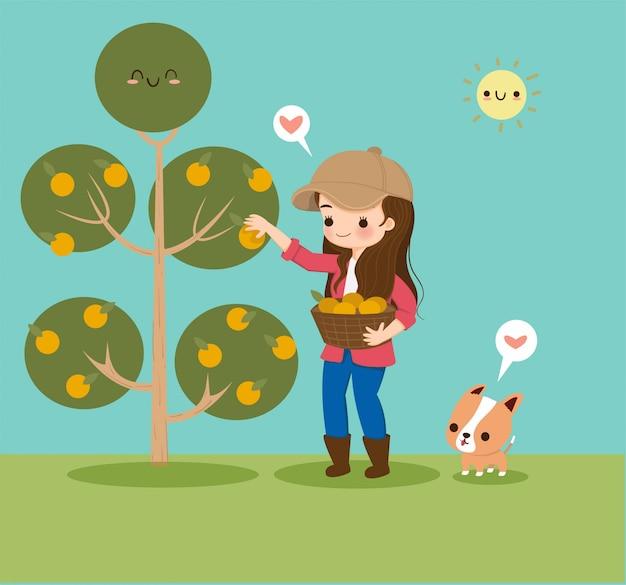 Linda garota reunindo frutas laranja no jardim com um cachorro