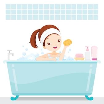 Linda garota tomando banho na banheira com espuma de sabão