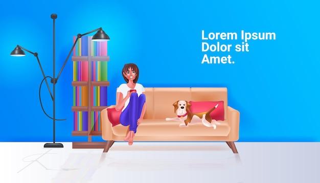 Linda mulher bebendo café garota relaxando com o cachorro no sofá ilustração vetorial horizontal de cópia espaço de corpo inteiro