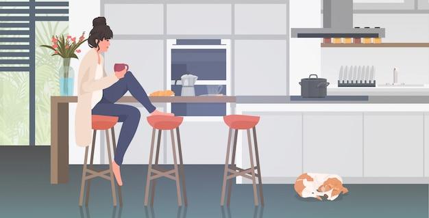 Linda mulher bebendo menina café sentado no banquinho no balcão cozinha moderna interior comprimento total