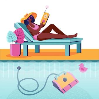 Linda mulher deitada em uma espreguiçadeira controla um robô para limpar piscinas