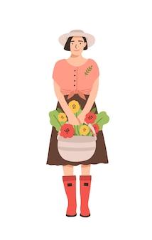 Linda mulher sorridente com botas de borracha, segurando uma cesta cheia de flores desabrochando.