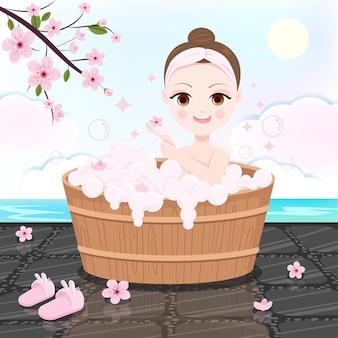 Linda mulher tomando banho nas flores de cerejeira