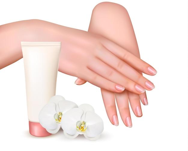 Lindas mãos femininas jovens com um creme e orquídeas.