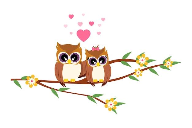 Lindo casal de corujas em pé com formas de coração em uma árvore de flores