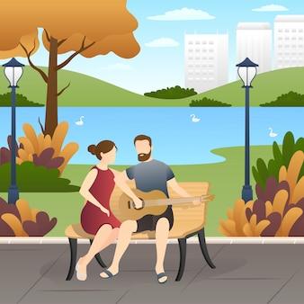 Lindo casal sentado no banco e tocando violão no parque.