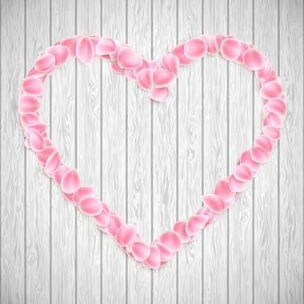 Lindo coração feito de pétalas de sakura rosa na textura de madeira.