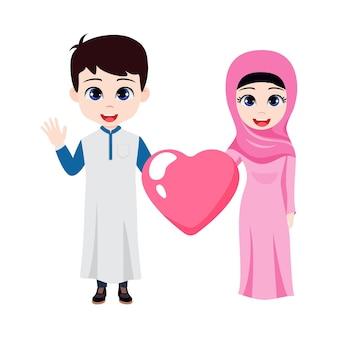 Lindo lindo garoto árabe e um casal de garotas em pé, acenando e segurando em forma de coração com vestido tradicional isolado