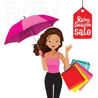 Liquidação de estação chuvosa, mulher de pele escura sob o guarda-chuva com muitas sacolas de compras