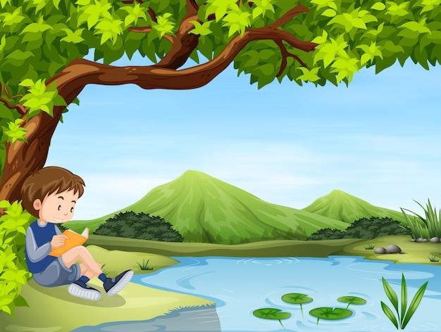 Livro de leitura de menino pela lagoa