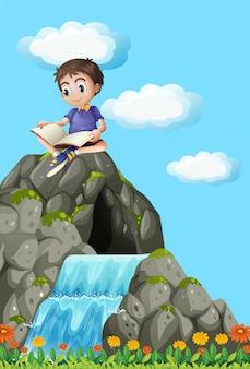 Livro de leitura do menino na rocha