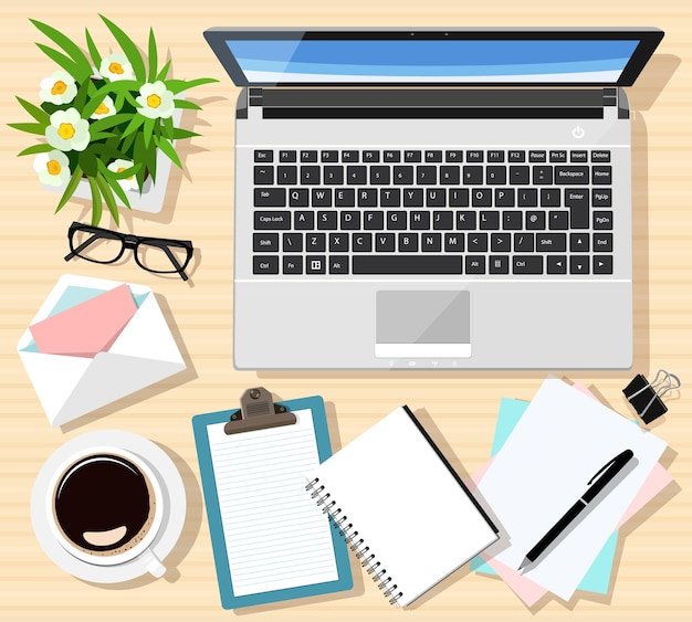 Local de trabalho moderno com mesa de madeira, laptop, notas, xícara de café, tablet, óculos, caneta, envelope, flores.