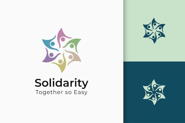 Logotipo da caridade ou juntos na mão e o sol representam paz ou solidariedade