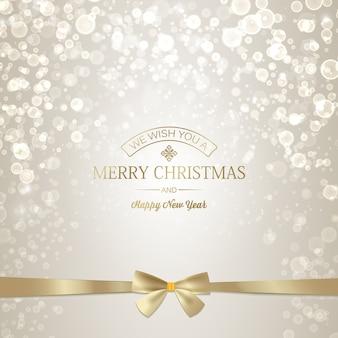 Luz de feliz ano novo e cartão de natal com inscrição dourada e laço de fita