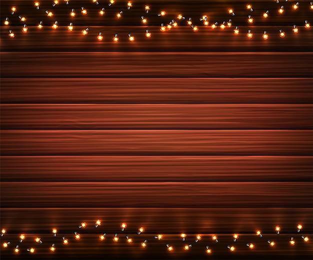 Luzes de natal. guirlandas de natal brilhante de lâmpadas led em fundo de textura de madeira