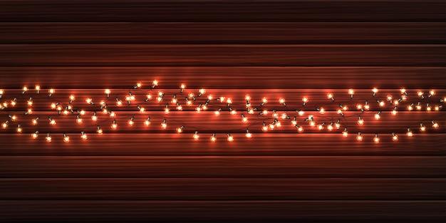 Luzes de natal. guirlandas de natal brilhante de lâmpadas led na textura de madeira.