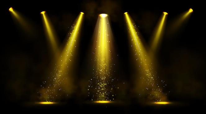 Luzes de palco, holofotes dourados com fumaça e brilhos.