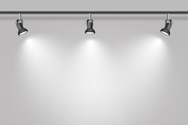 Luzes do ponto no fundo da parede branca do estúdio