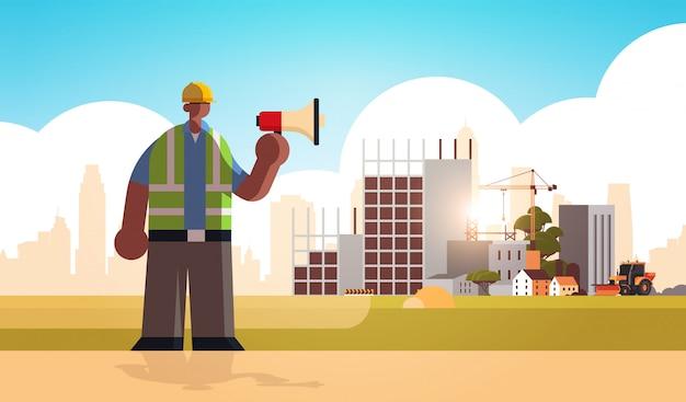 Macho, construtor, megafone, ocupado, trabalhador, usando, alto-falante, anúncio, trabalhador industrial, uniforme, construção, conceito, local construção, fundo, apartamento, comprimento cheio horizontal