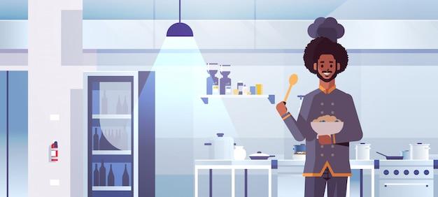 Macho profissional chef cozinheiro segurando a placa com mingau e colher homem afro-americano em uniforme degustação prato conceito de comida retrato moderno restaurante cozinha interior