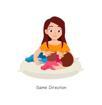 Mãe amamentando bebê gêmeo com pose nomeada na mesma direção