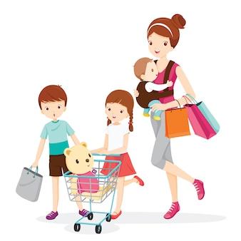 Mãe carrega bebê, filha empurrando carrinho de compras, filho com sacola de compras, família de compras juntos