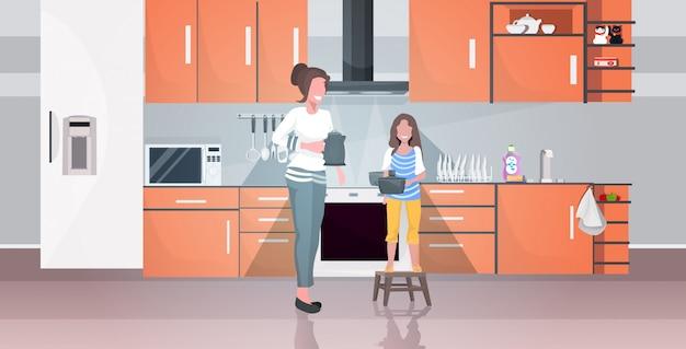 Mãe com filha segurando chaleira fazendo trabalhos domésticos