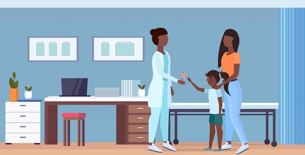Mãe com filha visitando médico pediatra dando pirulito para menina consulta conceito de saúde moderno hospital interior comprimento total horizontal