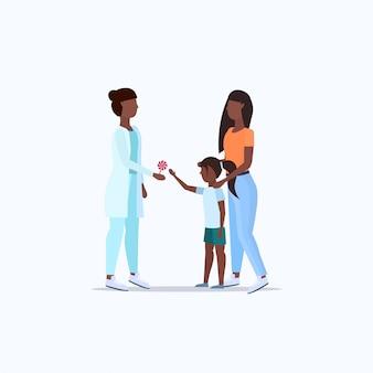 Mãe com filha visitando médico pediatra dando pirulito para menina consulta cuidados de saúde comprimento total