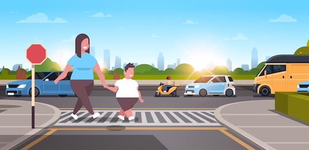 Mãe com filho andando cidade urbana rua família cruzando a estrada no conceito de obesidade de faixa de pedestres