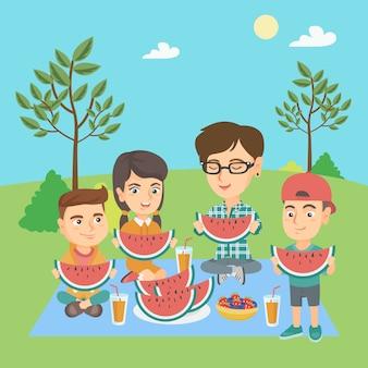 Mãe com filhos comendo melancia no parque.