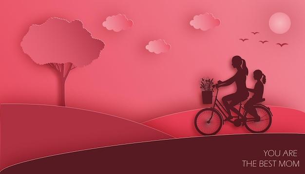 Mãe e filha andam de bicicleta com buquê de flores do prado no fundo do céu nublado vermelho