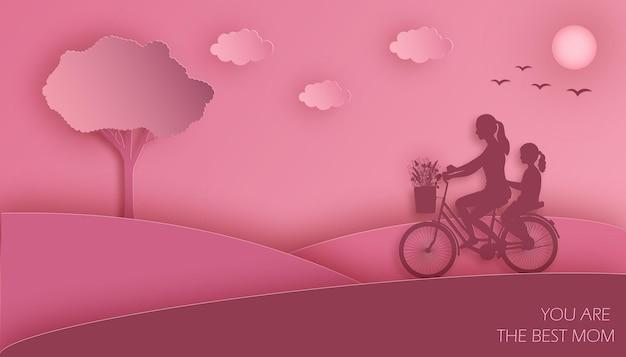 Mãe e filha andam de bicicleta com um buquê de flores do prado no fundo rosa do céu nublado