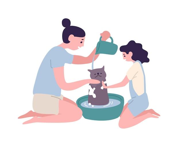 Mãe e filha felizes lavando gato em casa