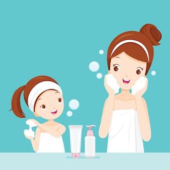 Mãe e filha limpando e cuidando do rosto