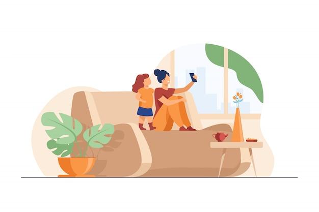 Mãe e filha usando smartphone para bate-papo por vídeo em casa