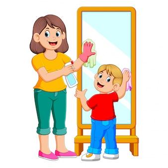 Mãe e filho limpando o espelho usando algum spray