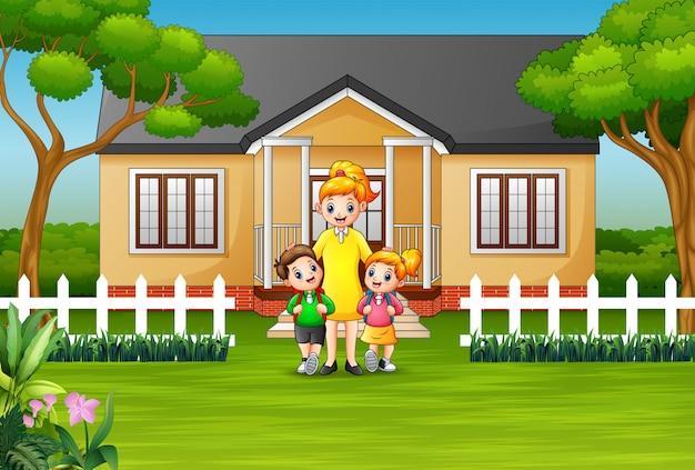 Mãe e filhos na frente de uma casa