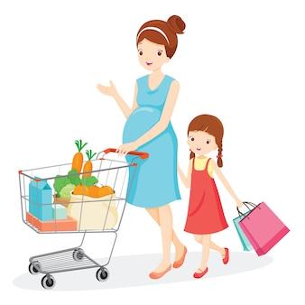 Mãe grávida, empurrando o carrinho de compras, filha com sacos de compras, família de compras juntos