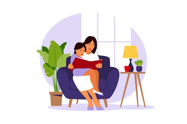 Mãe lendo para filha sentada no sofá com o livro.