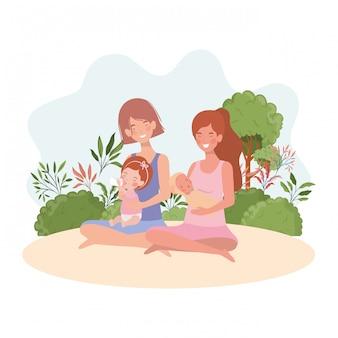 Mães de gravidez bonito sentado levantando bebês no acampamento