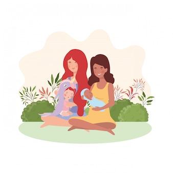 Mães grávidas inter-raciais sentadas levantando bebês no campo