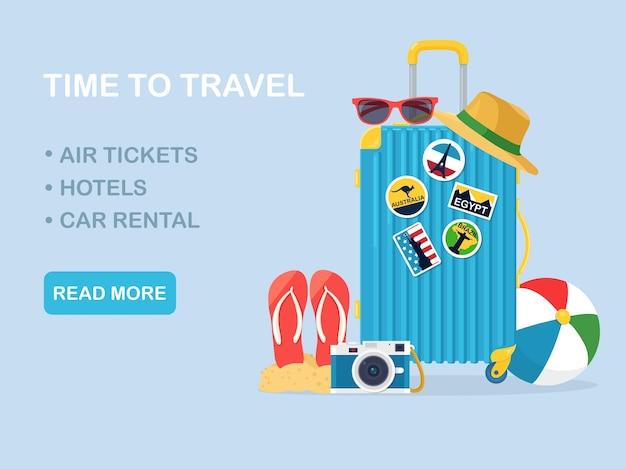 Mala de viagem, bagagem isolada no fundo. mala com adesivos, chapéu de palha, bola de praia, sandálias, sapatos, óculos de sol, câmera, bóia salva-vidas. horário de verão, férias, conceito de turismo. design plano