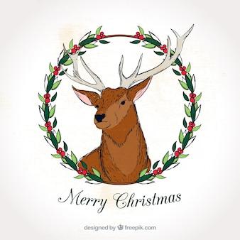 Mão cartão dos cervos feliz natal desenhado com coroa de flores