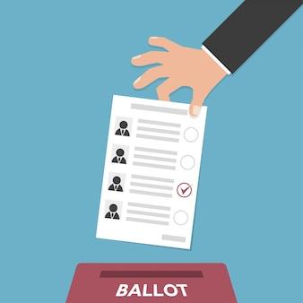 Mão coloca boletim de voto em caixa de votação