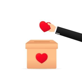 Mão colocando coração na caixa para doações