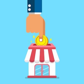 Mão colocando moedas na loja de negócios